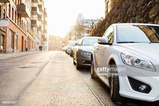 cars parked on street in city - parking stock pictures, royalty-free photos & images