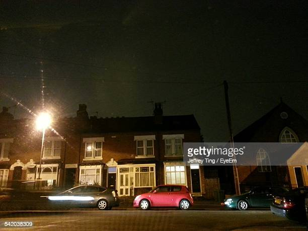 Cars Parked On Street Outside House At Night