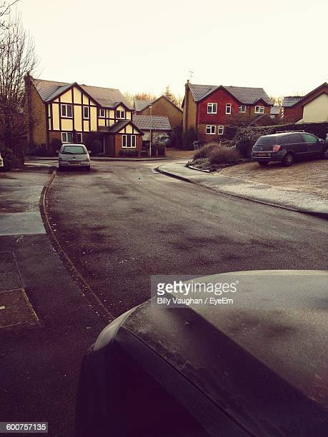 Cars Parking On Roadside In Residential District Against Sky