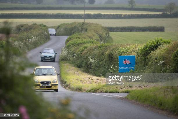 Cars pass a Conservative party campaign board that has been erected besides the road near the village of Holcombe on May 24 2017 in Somerset England...