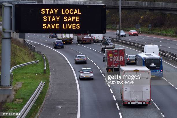 Cars pass a Covid warning sign on the eastbound M8 motorway in Glasgow ahead of the introduction of further coronavirus restrictions on November 20,...