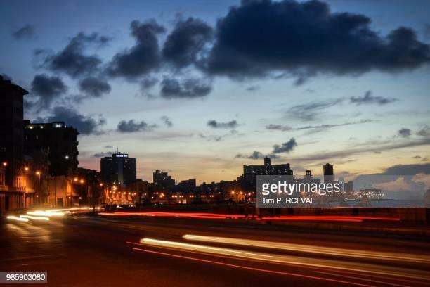Cars pass along the Malecon dusk Havana