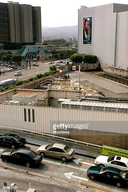 Cars pass an active oil well in between the Macy's and Bloomingdale's stores at the Beverly Hills Center shopping mall in Los Angeles California US...