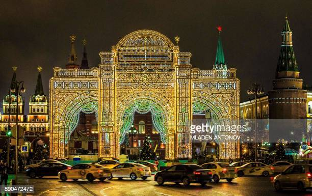 Cars pass next to an illuminated replica of the facade of the city's Maly Theatre installed in front of the Kremlin in Moscow on December 11 2017...