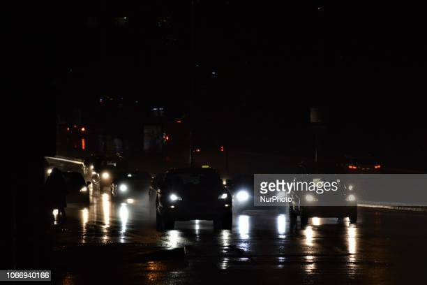 Cars pass through a raindrenched road illuminated by the headlights during a heavy rainfall in Ankara Turkey on November 30 2018 Torrential rainfalls...