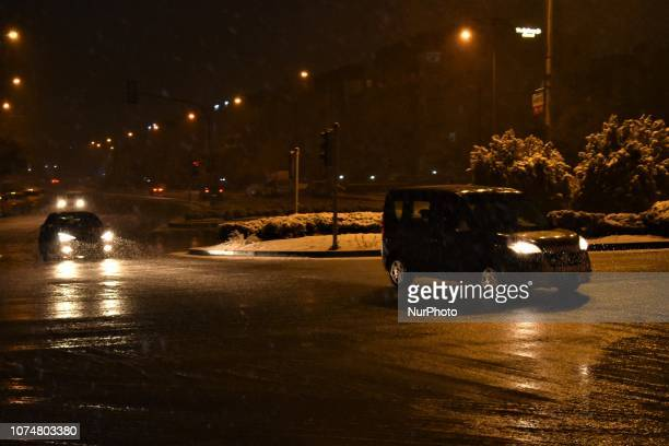Cars pass through a road intersection during a heavy snowfall in the winter season in Ankara Turkey on December 25 2018