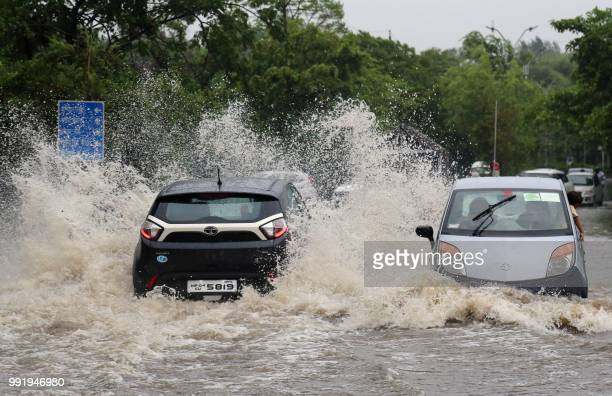 Cars pass through a waterlogged street in the central Indian city of Bhopal on July 5 2018 The monsoon is bringing heavy rains across the Indian...