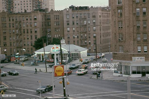 Cars pass through an intersection near Amoco and Shell gas stations with the storefront of August and Zelkinson glass company visible in the Bronx...