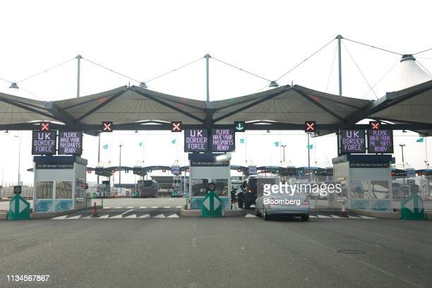 Cars pass through the U.K. Border control gates in the Port of Calais as UK Border Force digital signs advises drivers to have their passports ready...