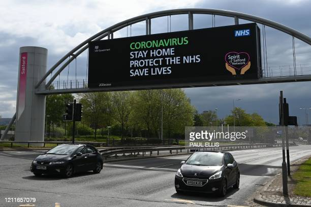 """Cars pass under a bridge where a large screen displays a message instruction people to """"stay home"""" in Salford on May 3 during the nationwide lockdown..."""