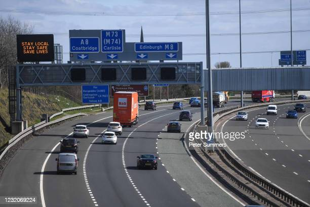 Cars pass under a motorway gantry notice on the M8 reading 'Stay Local, Stay Safe, Save Lives' on April 2, 2021 in Glasgow, Scotland. From today,...