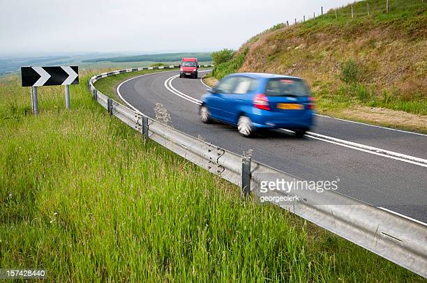 cars passing on a corner - moving past stock photos and pictures