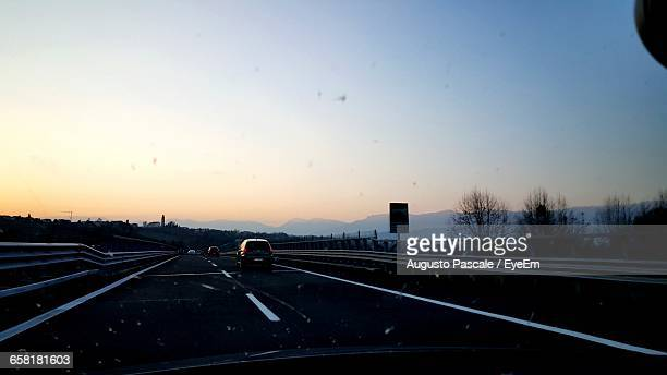 Cars Passing Through Highway With Mountains In The Background