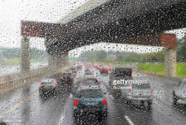 Cars passing under a viaduct on interstate 95 during a heavy rainfall.