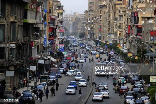 Cars pedestrians are pictured in one of the Egyptian capital Cairo's popular streets, shortly before the first day of a two-weeks night-time curfew...