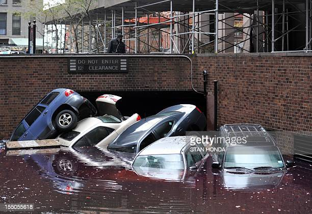 Cars piled on top of each other at the entrance to a garage on South Willliam Street in Lower Manhattan October 31 2012 in New York as the city...