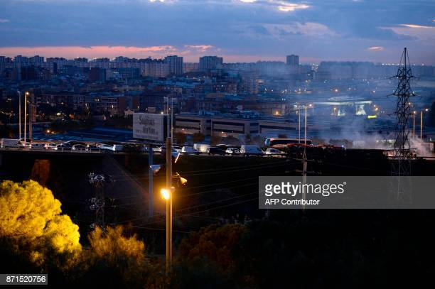 Cars queue as firemen try to extinguish a fire burning at a picket on the Ronda de Dalt road in Barcelona during a general strike to protest the...