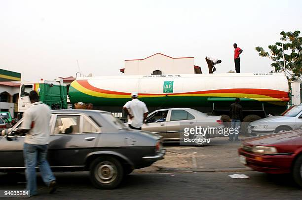 Cars queue for petrol as workers unload fuel from a tanker at an AP petrol station in Abuja Nigeria Tuesday December 12 2006 OPEC the producer of 40...