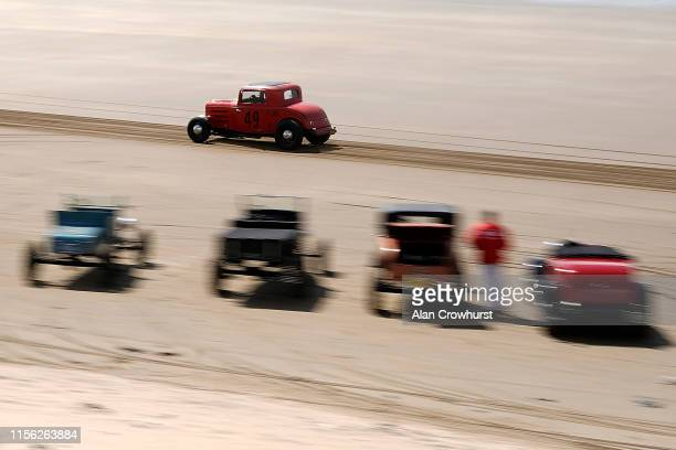Cars race along a straight mile course during the Vintage Hot Rod Racing on Pendine Sands on June 16 2019 in Carmarthen Wales