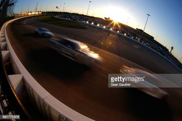 Cars race as the sun sets during the Monster Energy NASCAR Cup Series Go Bowling 400 at Kansas Speedway on May 13 2017 in Kansas City Kansas