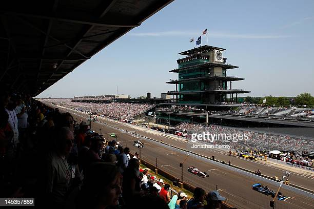 Cars race down the frontstretch past fans in the grandstands during the IZOD IndyCar Series 96th running of the Indianapolis 500 mile race at the...