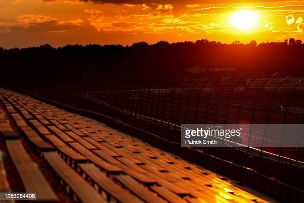 Cars race during sunset in front of empty grandstand spectator seating during the NASCAR Cup Series Pocono 350 at Pocono Raceway on June 28, 2020 in...