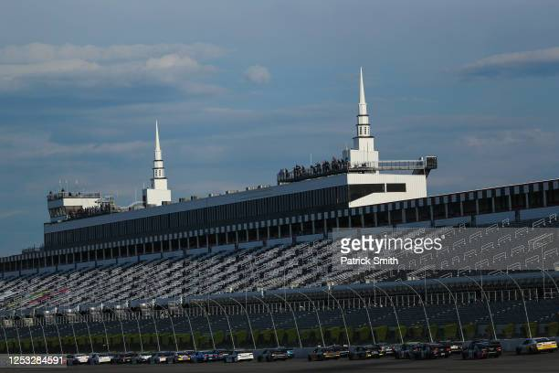 Cars race in front of an empty grandstand during the NASCAR Cup Series Pocono 350 at Pocono Raceway on June 28, 2020 in Long Pond, Pennsylvania. The...