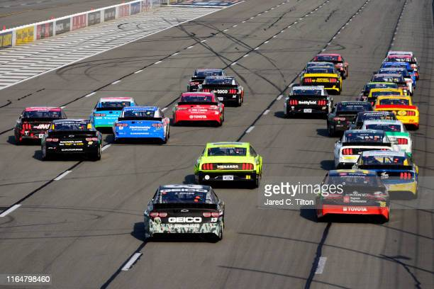 Cars race into turn one during the Monster Energy NASCAR Cup Series Gander RV 400 at Pocono Raceway on July 28 2019 in Long Pond Pennsylvania