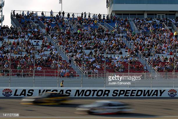 Cars race past fans during the NASCAR Nationwide Series Sam's Town 300 at Las Vegas Motor Speedway on March 10 2012 in Las Vegas Nevada