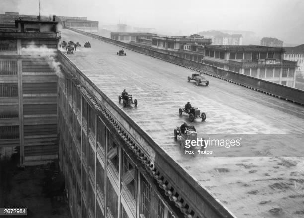Cars racing around the oval track on the rooftop of the Fiat works in Turin Northern Italy built for testing its cars December 1929 The factory was...