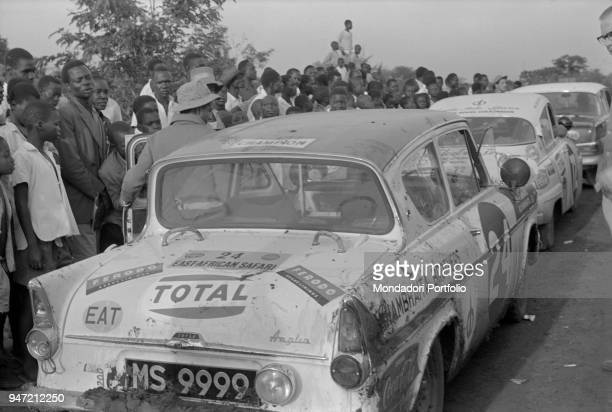 Cars running the East African Safari Rally standing at a block Kenya April 1965