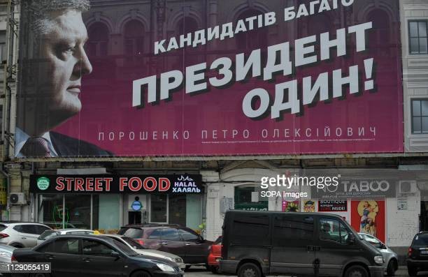 Cars seen going by a political billboard of Ukrainian presidential candidate Petro Poroshenko saying There are many candidates the President is one...