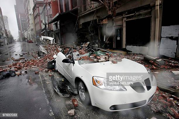 Cars sit along a side street damaged by falling debris in the French quarter of New Orleans 29 August 2005 as Hurricane Katrina makes landfall...