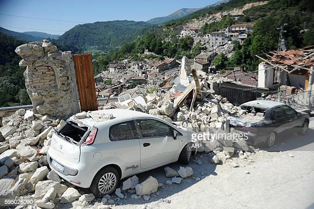 Cars sit amidst the rubble from earthquake damaged buildings in the central Italian village of Pescara del Tronto on August 25,2016 a day after a...