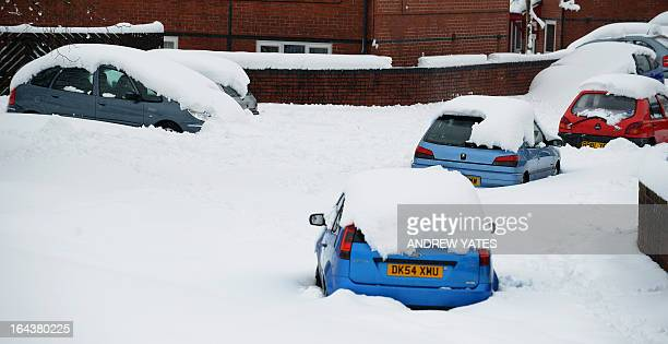 Cars sit burried in deep snow in Mold Flintshire north Wales on March 23 2013 Heavy unseasonal snow caused fresh disruption in Britain on March 23...