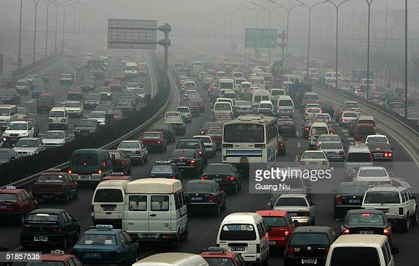 Cars sit in gridlock in heavy fog on December 14 2004 in Beijing China The bad weather has made it harder for Beijing to achieve the target of 18...