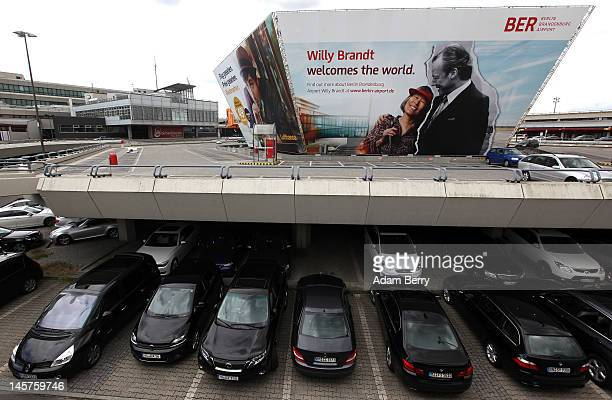 Cars sit parked in front of a billboard advertising the new Berlin Brandenburg Airport at Tegel airport on June 5 2012 in Berlin Germany Due to the...