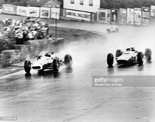 Cars speed on the rain soaked track during the Belgium Grand Prix in a scene from the film 'Grand Prix' 1966