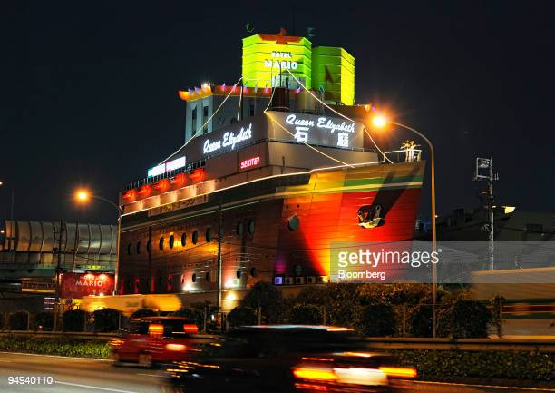 Cars speed past the Queen Elizabeth Sekitei love hotel on the outskirts of Tokyo Japan on Monday April 20 2009 While Japanese companies have...