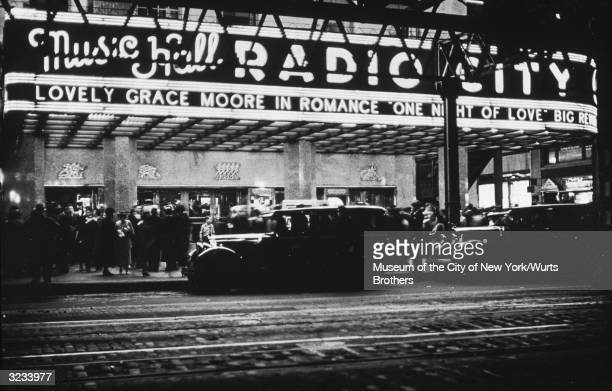 Cars stand in front of a crowded Radio City Music Hall with a marquee advertising Gracie Moore in the film 'One Night of Love' New York City
