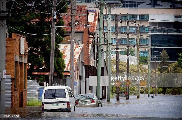 Cars stand partly submerged in floodwaters on a street in the inner Brisbane suburb of Newmarket on January 28 2013 Helicopters plucked dozens of...
