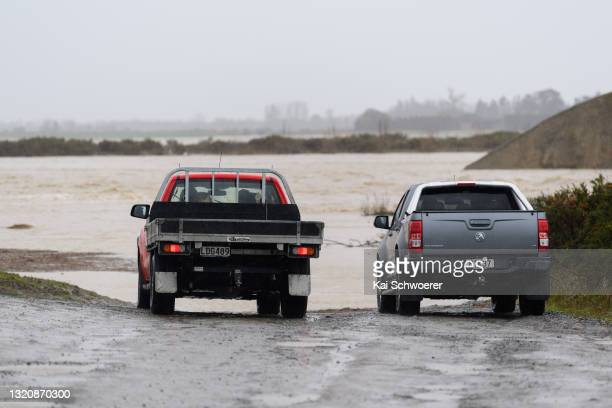 Cars stop in front of the flooded shingle pit where the Selwyn River usually flows underground on May 31, 2021 in Greendale, New Zealand. Heavy rain...