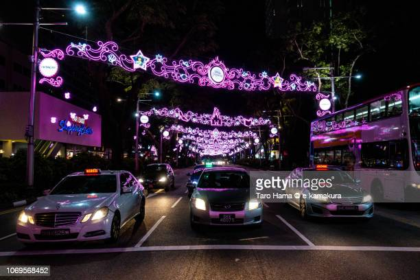 Cars stopping under illuminated Orchard Street in Singapore