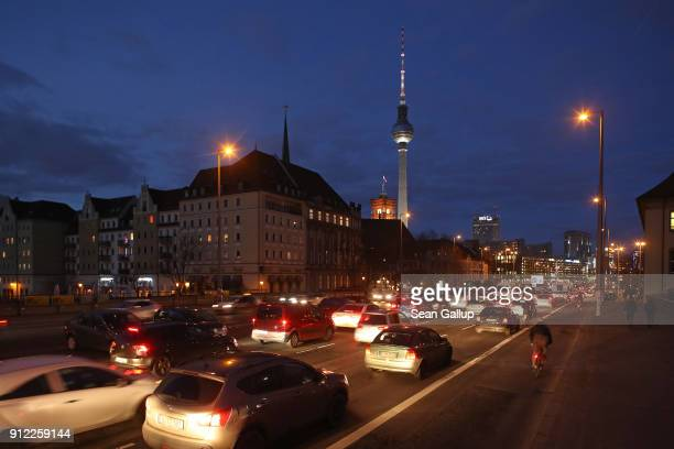 Cars stream along Leipziger Strasse as the broadcast tower at Alexanderplatz stands behind in the city center on January 30 2018 in Berlin Germany A...