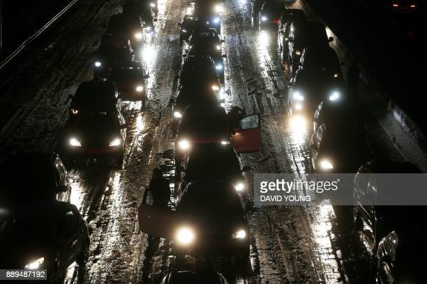 TOPSHOT Cars stuck in a jam on the A3 highway in Duesseldorf western Germany after snowfall on December 10 2017 / AFP PHOTO / dpa / David Young /...