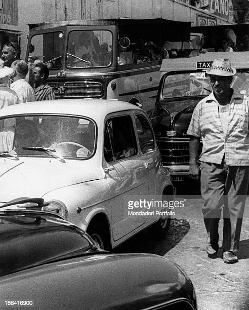 Cars taxis and buses clog a street in Marina Grande some people walk nearby Capri Italy 1962