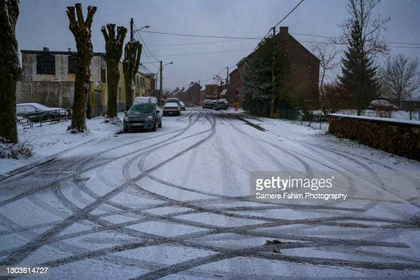cars tires tracks marking a road covered by snow in winter - hainaut stock pictures, royalty-free photos & images