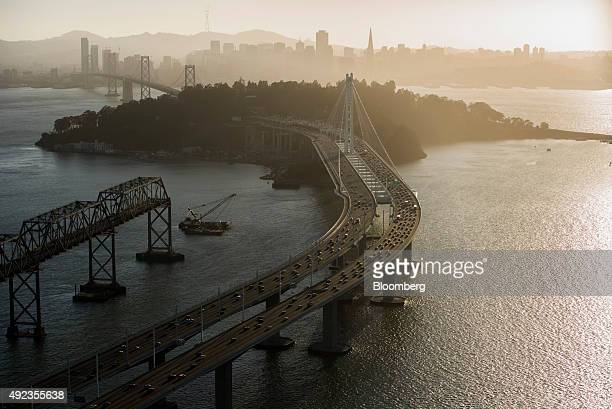 Cars travel over the San FranciscoOakland Bay Bridge towards Treasure Island in this aerial photograph taken above San Francisco California US on...