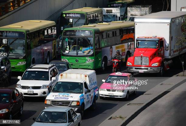 Cars trucks and buses drive in rush hour traffic on a freeway in Mexico City on December 6 2017 / AFP PHOTO / David GANNON
