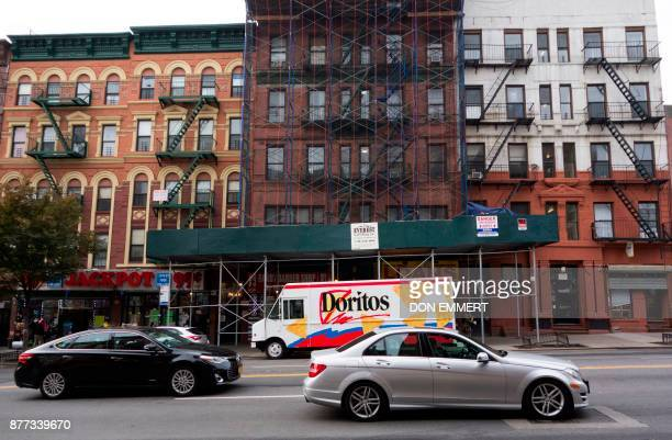 Cars wait at a stoplight on 116th St in Harlem as building reconstruction takes place November 14 2017 in New York Harlem was the neighborhood where...